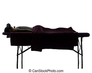 massage therapist - one woman lying on a massage table in...