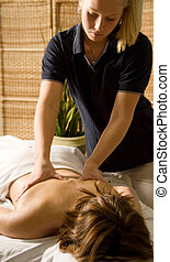 Massage therapist - woman in a day spa getting a back...