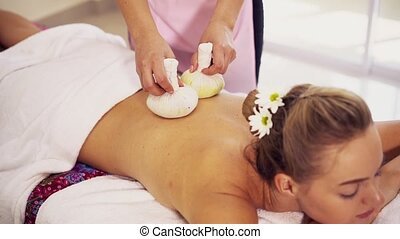 Massage therapist using herbal compress on woman. - Massage ...