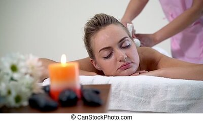 Massage therapist uses a herbal compress to do treatment to woman lying on spa bed in a luxury spa resort. Wellness, stress relief and rejuvenation concept.