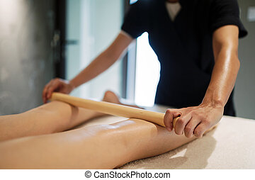 Massage therapist using wooden tool to massage patient