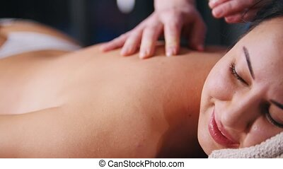 Massage treatment. A woman client lays on the couch and...
