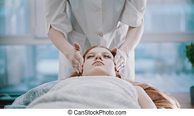 Massage - young masseuse is holding a massage with her client