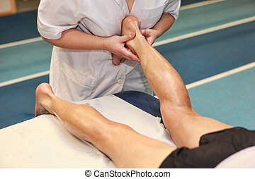 massaging athlete Achilles tendon - masseuse massaging...