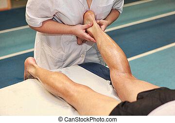 massaging athlete Achilles tendon - masseuse massaging...