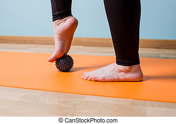 Closeup woman's barefoot legs rolling small black knobbed ball. Self myofascial release to smooth muscle spasm. The girl leans a foot on the black Myofascial Ball.
