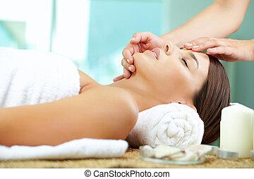 Massaging face - Young woman enjoying facial at spa salon