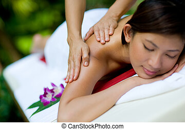 Massaging Hands - A young woman having massage outside in...