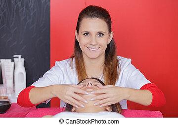 masseur doing massage the head of an adult woman