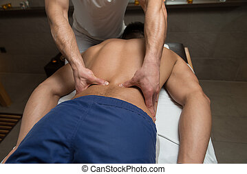 Masseur Giving Back Massage To A Man