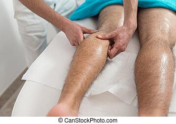 Masseur Giving Legs Massage To A Man