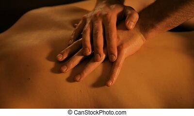 Masseur hands doing back massage in spa center - Close-up...