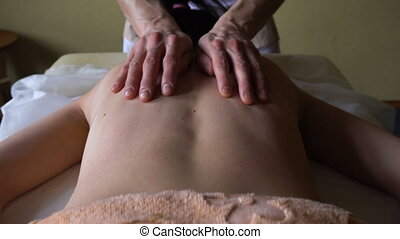 Masseur Kneads the Back of Young Woman With Warm Oil on at Professional Massage Session. Ayurvedic Abyanga massage.