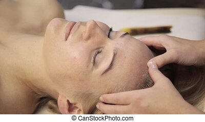 masseur makes acupressure on a female face. Chinese...