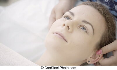 Masseur makes massage of auricle at woman in spa salon.