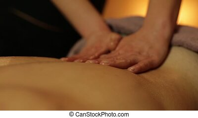 Masseur makes massage with oil for man