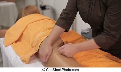 Masseur massages client's thigh at the cosmetology centre