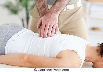 Masseur massages customer's back - A masseur massages a...