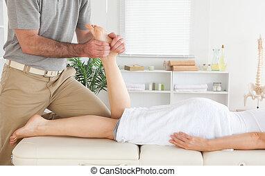 Masseur massages customer's leg