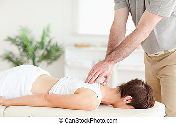 Masseur massaging a female customer's back