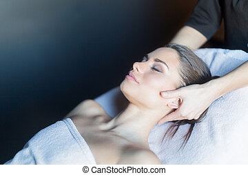 Masseur massaging face of a beautiful, young woman lying on the massage table