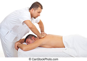 Masseur massaging man back at spa