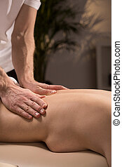 Masseur massaging naked woman
