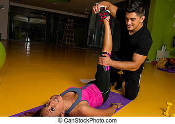 Masseur stretching woman's leg - A massage therapist helps...