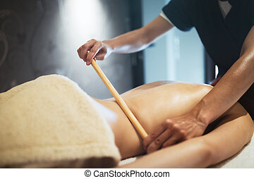 Masseur using massage bamboo sticks