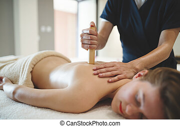 Masseur using sticks and rods to massage