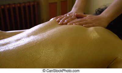 Masseur Woman Makes Massage of Back with Warm Oil to a Young Man