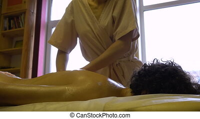 Masseur Woman Makes Massage of Hands and Shoulders to a Young Man