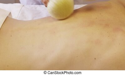 Masseur's hands are massaging on the girl's back at spa salon