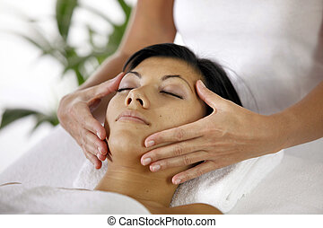 Masseuse giving face massage