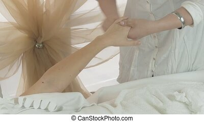 Masseuse make massage of fingers on left woman hand in...