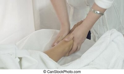 Masseuse make massage of left feet to woman in saloon. Therapeutic procedure
