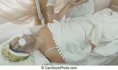 Masseuse make massage of left woman hand in beauty saloon....