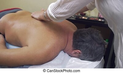 Masseuse make therapeutic massage of backbone to adult fat...