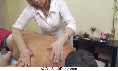 Masseuse make therapeutic massage to adult fat man. Pinch a...