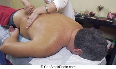 Masseuse make therapeutic massage to adult fat man. Stroking...