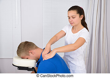 Masseuse Massaging Man's Shoulder
