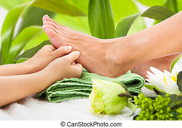 Cropped image of masseuse massaging woman's foot against leaves at spa