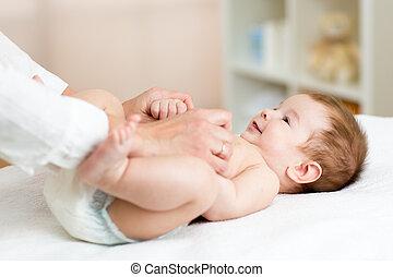 Masseuse or doctor massaging baby boy