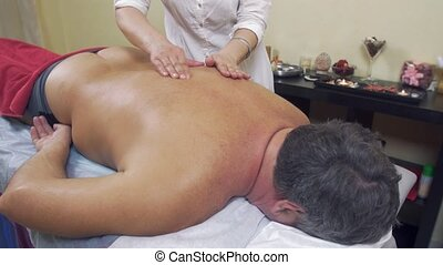 Masseuse rubdown backbone of adult fat man. Therapeutic...
