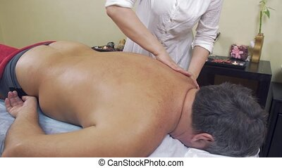 Masseuse rubdown neck of adult fat man. Therapeutic massage....