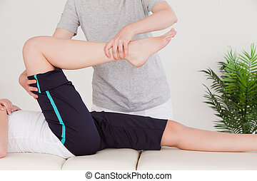 Masseuse stretching the right leg of a young woman
