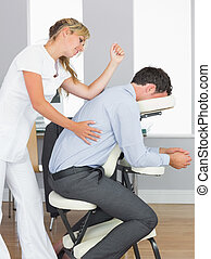 Masseuse treating clients back with elbow in massage chair...