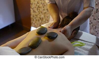 Masseuse using hot stone massage therapy