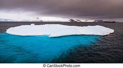 Massive iceberg with blue uderwater part and cruise ship in background, Peterman Island, Antarctica