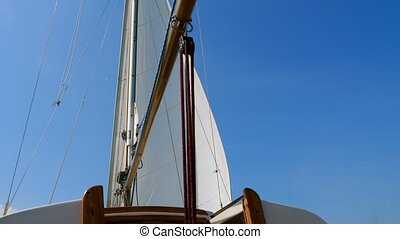 Mast and sail of a wooden yacht and summer sky.